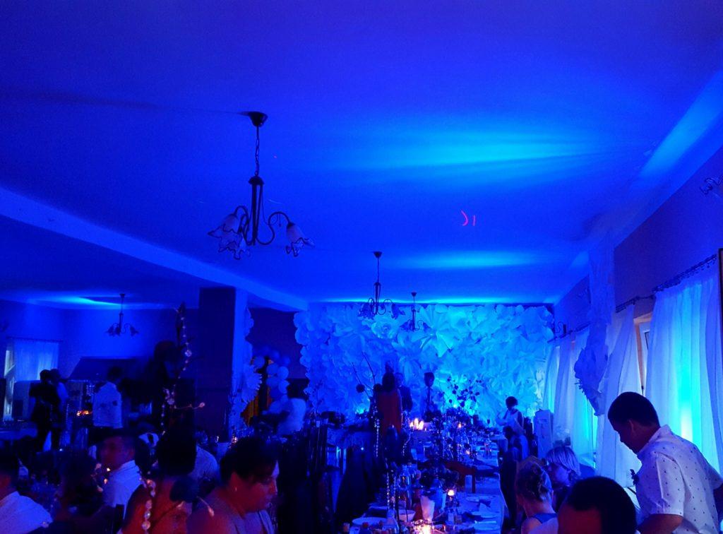Na życzenie Pary Młodej dekoracja światłem na niebiesko stołu Młodych i sali jadalnej.